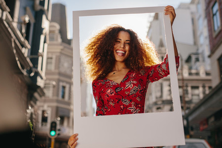 Funny young woman with a blank photo frame