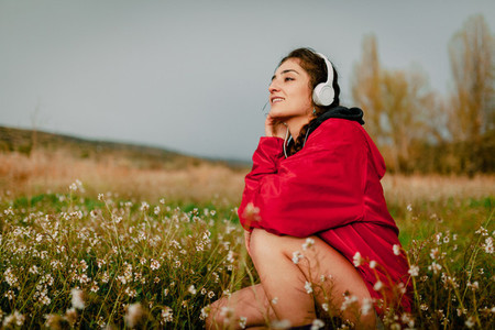 Girl listening to music with headphones sitting among wildflowers