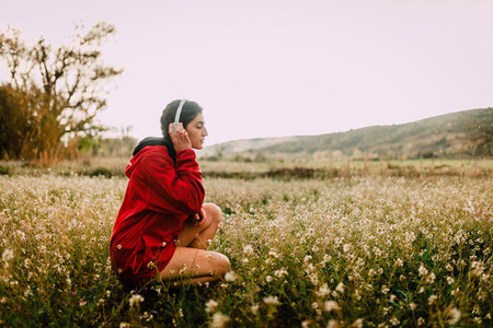 Girl listening to music with headphones sitting among wildflowers