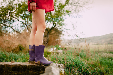 Closeup outdoors of girl legs with red raincoat and water boots