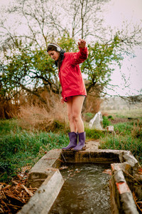 Girl with headphones and raincoat washing her waterproof boots