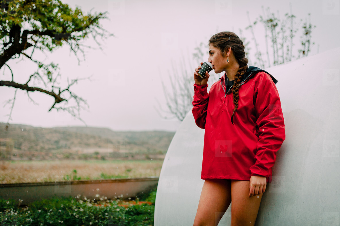 Girl with raincoat and tea in her orchard while it is raining