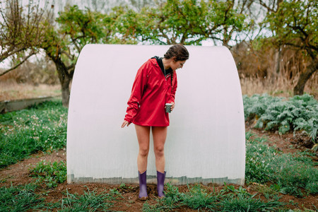 Girl with raincoat in her orchard while it is raining
