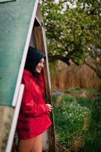 Smiling girl wearing red raincoat takes shelter from the rain