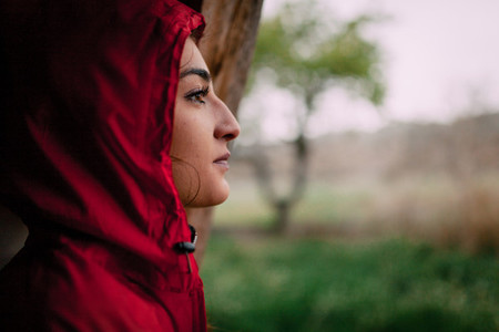 Girl wearing red raincoat observes the rain on the field