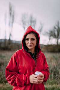 Smiling girl wearing a red raincoat on the field