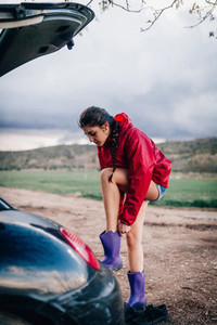 Girl putting her waterproof boots near her car