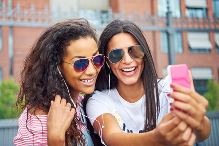 Two young girlfriends smiling and taking selfies together outside