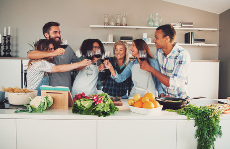Group of friends cheering at kitchen