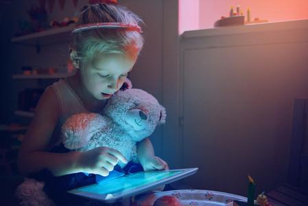 Amazed little girl holding bear browsing tablet