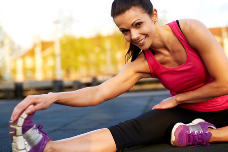 Woman doing a seated hamstring stretch smiling at camera