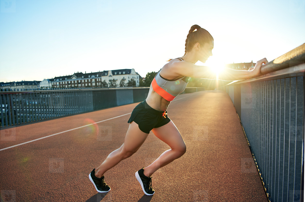 Female jogger stretches against bridge railing