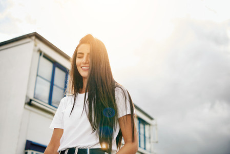 Happy young woman walking past building