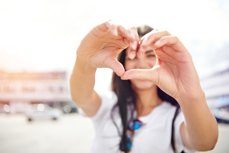 Romantic young woman making a heart gesture