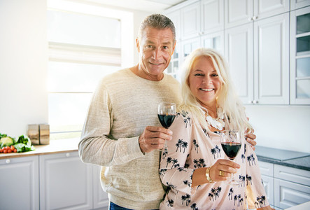 Smiling middle aged couple holding wine glasses