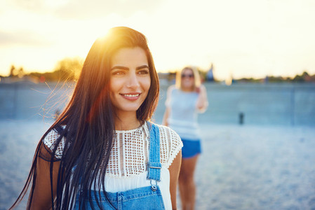 Grinning woman with friend out of focus behind her