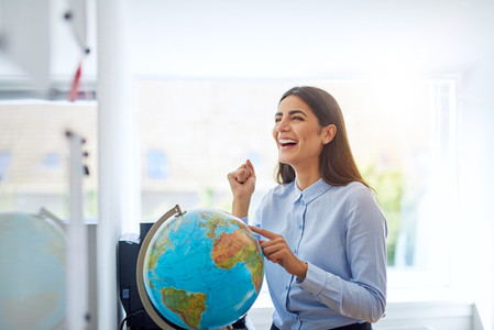 Laughing woman pointing to country on globe