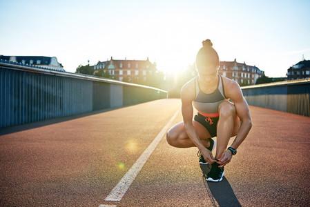 Muscular woman ties her running shoes on bridge