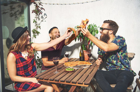 Friends toast with pizza and laugh while outside