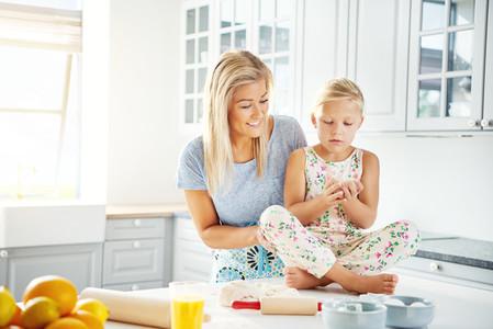 Happy woman helping little girl prepare food