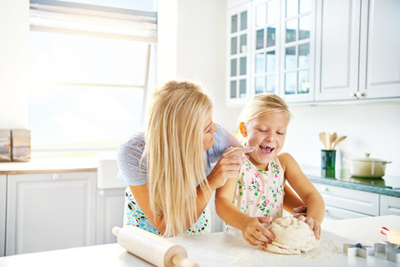 Laughing little girl helping her Mum knead dough