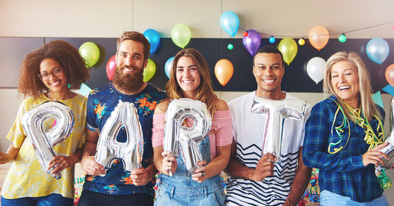 Friends holding balloons as letters for PARTY