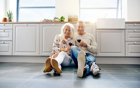 Laughing mature couple holding wine in kitchen