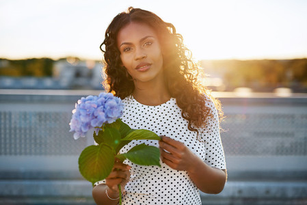 Pretty black woman presenting a flower