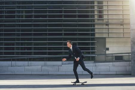 Successful man riding skateboard in the street