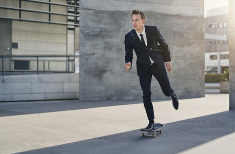 Confident successful man in suit riding skateboard