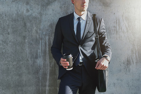 Businessman with beverage standing in the street