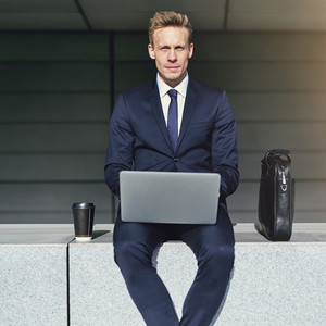 Handsome businessman with laptop looking at camera