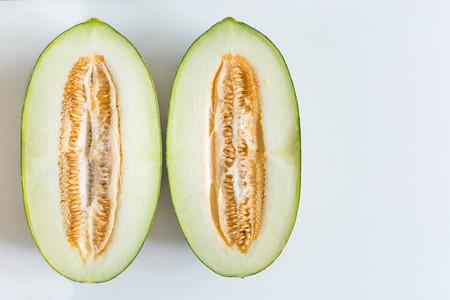Freshly cut honeydaw melon on a white background