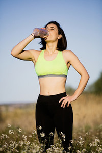 Girl drinking water wearing sporty clothes in the field