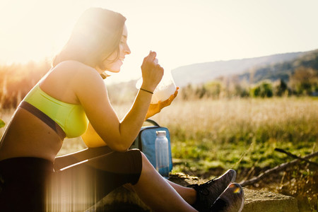 Young sporty woman eating healthy lunch in the field