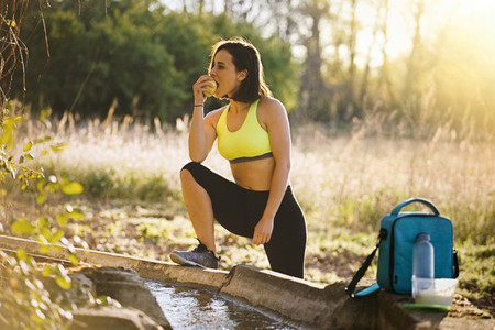 Young sporty woman eating an apple in the field