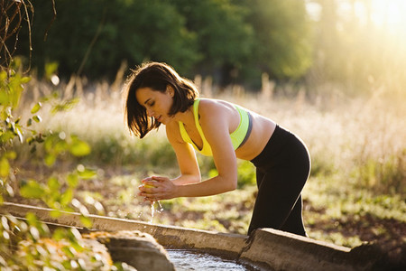 Young sporty woman washing an apple in the field