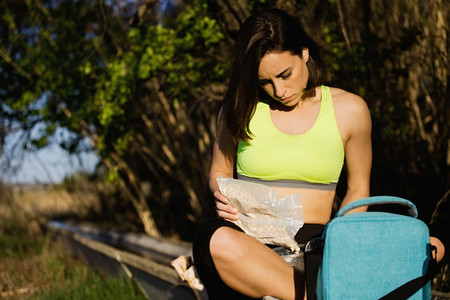 Young sporty woman preparing healthy lunch in the field