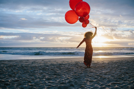 Woman on the beach with balloons