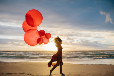 Woman running on the beach with balloons