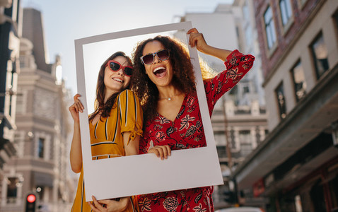 Girls posing with empty photo frame