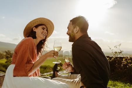 Couple sitting near a vineyard on a date drinking wine
