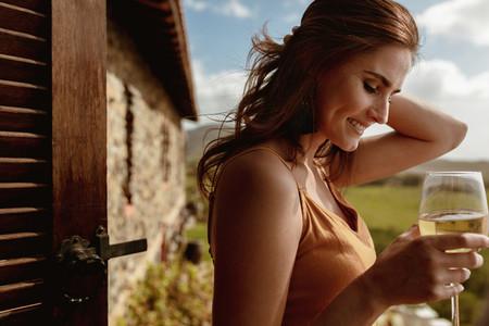 Woman enjoying a glass of wine standing outdoors