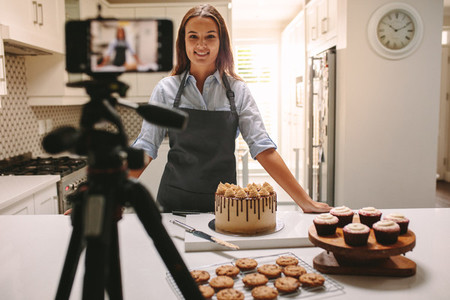 Woman recording vlog in kitchen