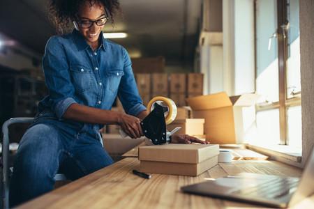 Entrepreneur packing parcel using tape dispenser