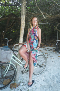 Smiling woman sitting on bicycle near tree