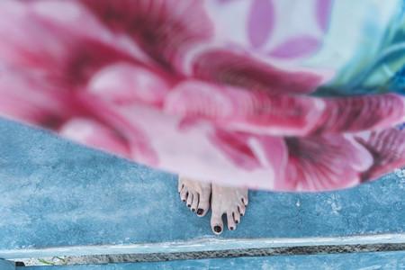 Crop barefoot female on shabby floor