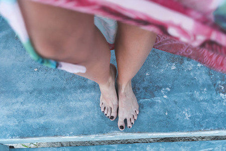 Crop barefoot female on shabby floor