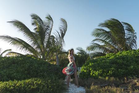 Woman near palms on windy day