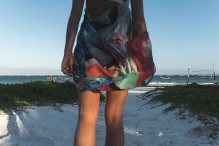 Anonymous female walking towards sea